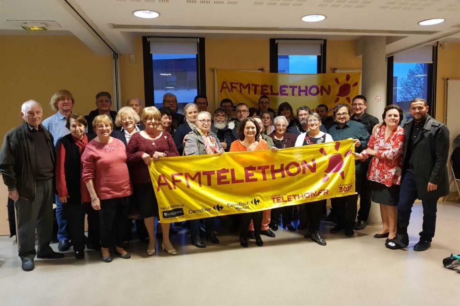 Un groupe de bénévoles posant derrière une banderole du Téléthon