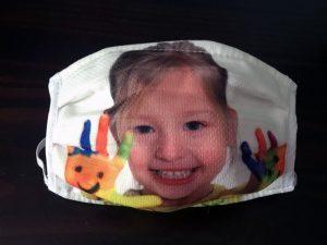masque en tissu réutilisable avec une petite fille souriante montrant ses mains pleines de peinture aux couleurs du Téléthon